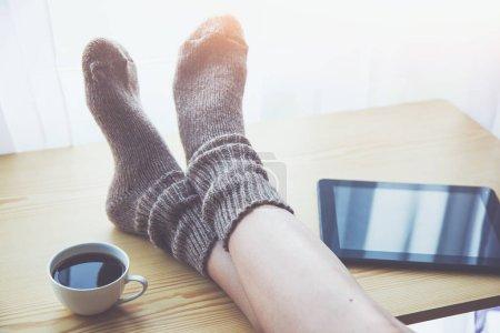 Photo pour Femme au repos gardant les jambes dans des chaussettes chaudes sur la table avec café du matin et lecture e-book ou tablette - image libre de droit