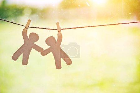 Photo pour En bois petits hommes suspendus sur corde avec épingle. Symbole d'amitié, aide, soutien et travail d'équipe - image libre de droit
