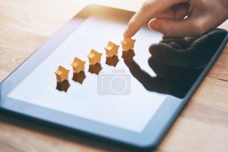 Photo pour Main donne cinq étoiles classement comme rétroaction de produit avec tablette - image libre de droit