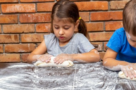 Photo for Little kids girl and boy dough, preparing dough for baking - Royalty Free Image