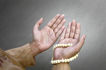 Muslim man praying with prayer beads over gray background