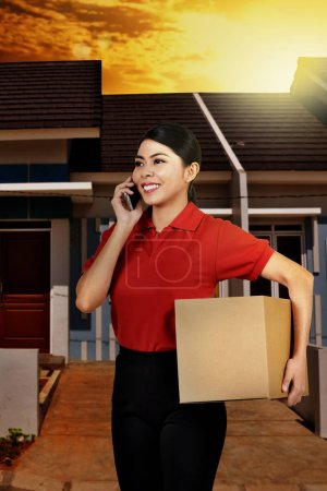 Smiling asian courier woman with phone holding parcel in front of house