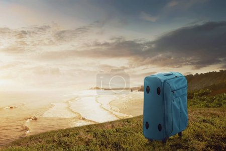 Blue suitcase on the cliff with seascapes view. Summer travel concept