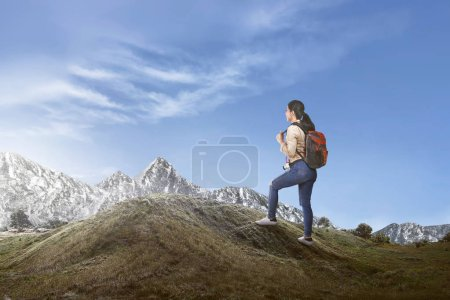 Happy asian female traveler with backpack walking to the top of the mountain