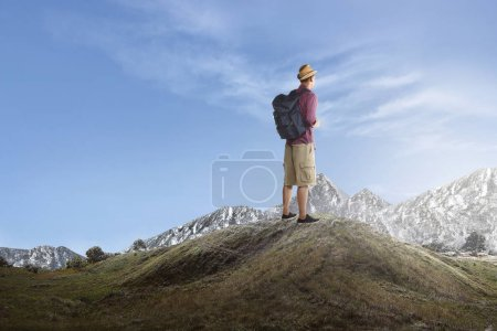 Rear view of asian traveler standing and enjoying view from top of hill