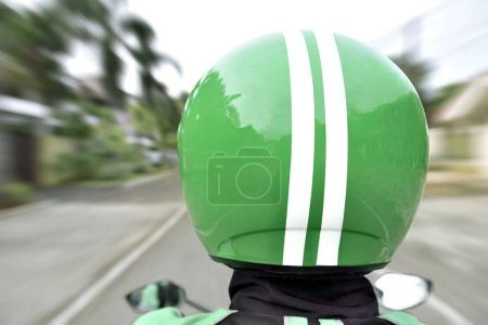 Rear view of motorcycle taxi ride with fast on the urban street