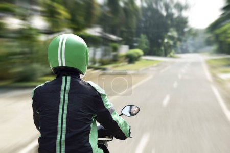 Rear view of motorcycle taxi driver rushing on the road