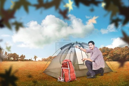 Young asian man set up a tent outdoors. Autumn recreation