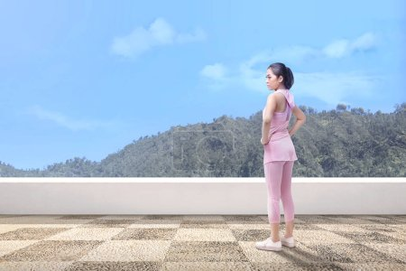 Young asian woman taking a break after running outdoor with green hills background