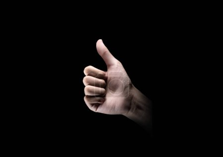 Photo for Hands showing thumb up gesture over dark background - Royalty Free Image