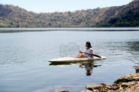 Asian lady paddling the kayak on the lake in satonda island. Sumbawa, Indonesia