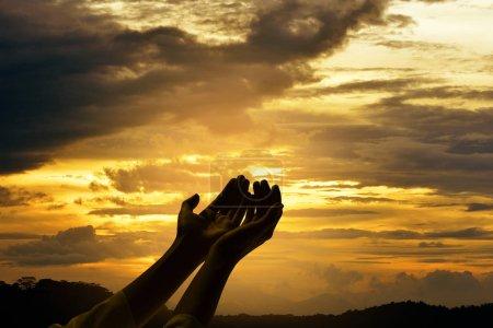 Photo pour Mains masculines avec la paume ouverte priant Dieu sur fond de lever de soleil - image libre de droit