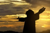 Silhouette of Jesus christ standing with raised arms at sunset background