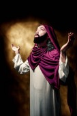 Jesus christ raised arms with open palm praying over dark background