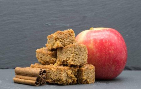 Photo pour Image de boulangerie contenant des bâtons de canelle de crêpes et une pomme rouge à l'arrière de l'image. Tout en étant situé sur l'ardoise où le focus est forte à l'avant puis tombe vers l'arrière de l'image.. - image libre de droit
