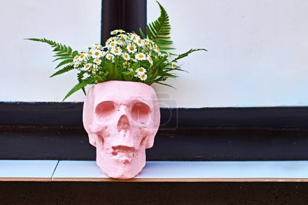 Flower pot in the form of a skull on a outdoor shelf at a street cafe