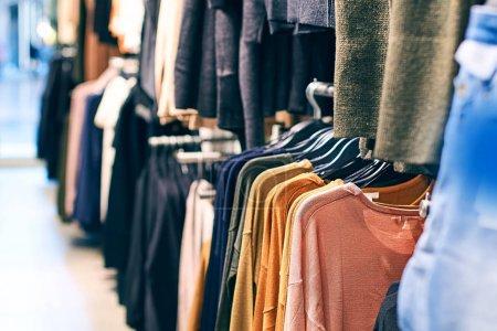 Photo pour Concept de tendance mode. Intérieur du magasin de vêtements avec différentes femmes vêtements sur cintres . - image libre de droit