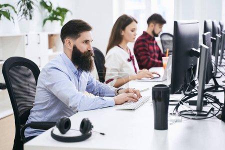 Photo pour Les gens qui travaillent dans un bureau informatique moderne. Groupe de jeunes programmeurs et développeurs de logiciels assis à des bureaux travaillant sur des ordinateurs. L'équipe au travail. - image libre de droit
