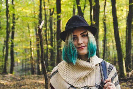 The girl is blonde with blue ends in knitted ethnic ponchos, skirts and a backpack. The warming of the atmosphere is warm and the sun.Portret in the woods. Natural background. Woman travels Travel  photo.