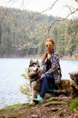 Rudy girl in the mountains in a poncho with a dog. Husky in the