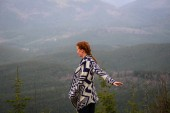 Rudy girl in the mountains in a poncho. Carpathian Mountains. Tr