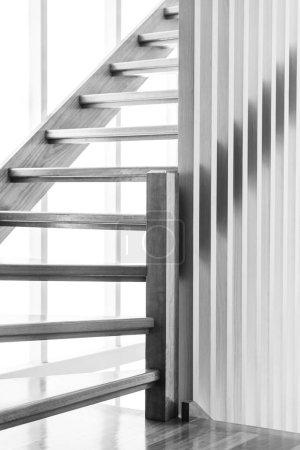 Photo pour Escalier intérieur en bois avec lumière derrière lui en noir et blanc - image libre de droit