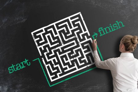 Photo for Finding creative and smart solutions concept with woman bypassing labyrinth by drawing line around it as workaround on blackboard - Royalty Free Image
