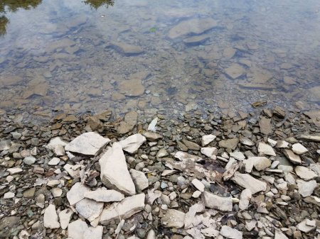 Broken grey rocks and water at shore of river or l...
