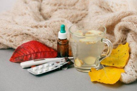 Teebecher mit warmem Schal, Thermometer und Nasentropfen, Tabletten auf gr