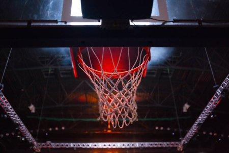 Photo pour Cerceau de basket-ball dans les néons rouges dans l'arène de sports pendant le jeu - concurrence - image libre de droit