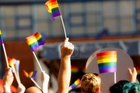 Photo pour Communauté de fierté lors d'un défilé avec les mains levées et le drapeau LGBT - symbole d'amour et de tolérance - image libre de droit