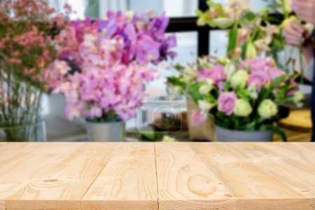 Foto de Empty wooden table space platform and blurred coffee shop where working and meeting place background for product display montage. - Imagen libre de derechos