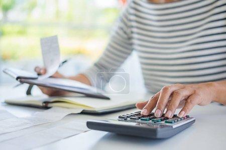 Photo pour Femme avec factures et calculatrice. Femme utilisant une calculatrice pour calculer les factures à la table au bureau. Calcul des coûts . - image libre de droit