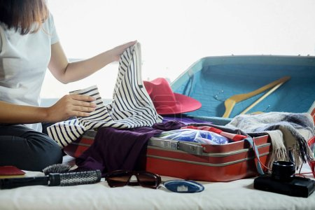 Photo for People packed suitcase with travel accessories on bed. Vacation concept - Royalty Free Image