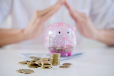 Photo pour Affaires de personnes abritant des pièces de monnaie et tirelire au bureau. concept de l'épargne - image libre de droit