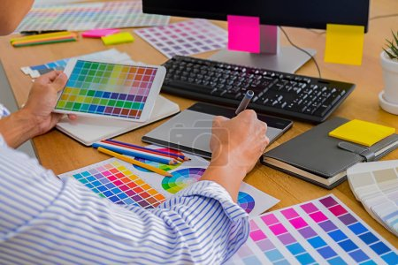 Photo pour Graphisme avec des nuances de couleur et une tablette sur un bureau. Graphiste, dessin quelque chose sur la tablette au bureau avec des outils de travail et accessoires. - image libre de droit