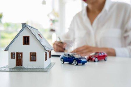 Photo pour Voiture et maison modèle avec agent et discuter pour contrat de client d'acheter, d'obtenir de l'assurance ou de prêt immobilier ou le fond de la propriété. - image libre de droit