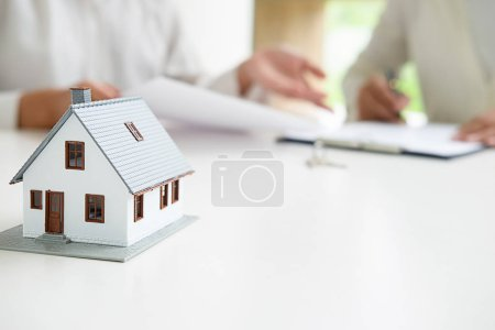 Photo for House model with real estate agent and customer discussing for contract to buy house, insurance or loan real estate background. - Royalty Free Image