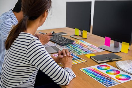 Photo for Graphic design with color swatches and tablet on a desk. Graphic designer drawing something on tablet at the office with work tools and accessories. - Royalty Free Image