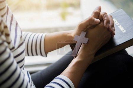 Photo pour Femme chrétienne priant sur la Sainte bible. Mains repliées dans la prière une sainte bible dans l'église concept - image libre de droit