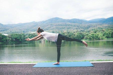 Photo pour Concept de yoga. Jeune femme médite tout en pratiquant l'yoga dans le parc. Calme et détente, bonheur féminin. jardin de flou sur le fond - image libre de droit