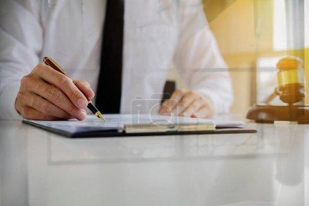 Photo pour Concept de justice et du droit. Conseiller juridique présente au client un contrat signé avec marteau et droit juridique ou morale ayant la réunion de l'équipe au cabinet juridique à fond - image libre de droit