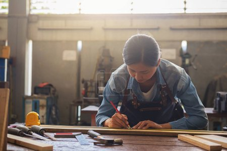 Photo for Carpenter working on woodworking machines in carpentry shop. woman works in a carpentry shop. - Royalty Free Image