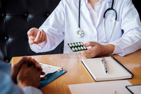 Photo pour Patient, écoutant attentivement un mâle médecin expliquant les symptômes du patient ou de poser une question comme ils discutent paperasse ensemble lors d'une consultation - image libre de droit