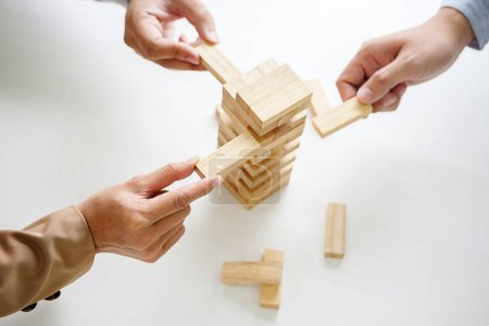 Photo for Hand of business people planning, risk and strategy in business.Businessman gambling placing wooden block on a tower. - Royalty Free Image