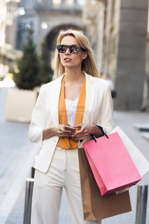 beautiful young blonde woman in sunglasses holding smartphone and shopping bags on street