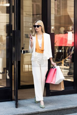 beautiful stylish young woman with shopping bags and smartphone standing in doorway of fashionable boutique