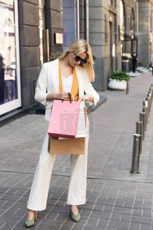Photo for Full length view of stylish young woman looking into shopping bags on street - Royalty Free Image