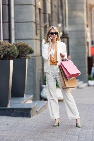 Photo pour Belle jeune femme souriante dans lunettes de soleil tenant des sacs à provisions et parlant de smartphone dans rue - image libre de droit