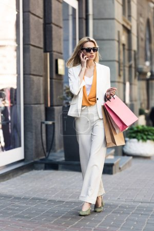 full length view of stylish beautiful blonde girl holding shopping bags and talking by smartphone on street